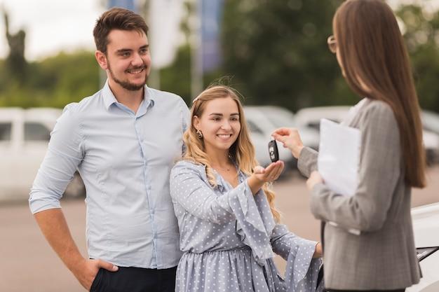 Concessionario auto femminile offrendo le chiavi per una coppia Foto Gratuite