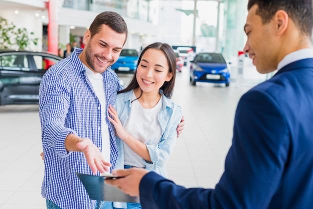 Concessionario di auto parlando con i clienti Foto Gratuite