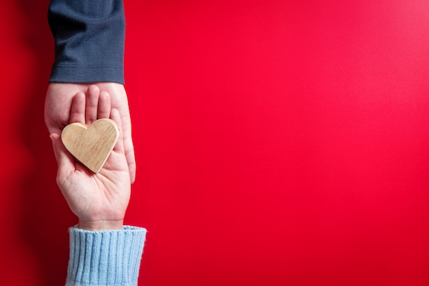Concetti d'amore, coppia in amore con il cuore sulle mani sul rosso Foto Premium