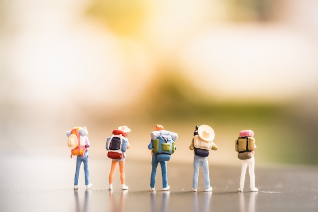 Concetti di viaggio il gruppo di mini figure miniatura del viaggiatore con lo zaino ed il cappello stanno su terra Foto Premium