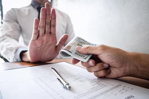 Concetto anti corruzione e corruzione, uomo d'affari che rifiuta e non riceve banconote in denaro nell'involgere l'offerta da parte degli uomini d'affari di accettare un contratto di accordo di investimento Foto Premium