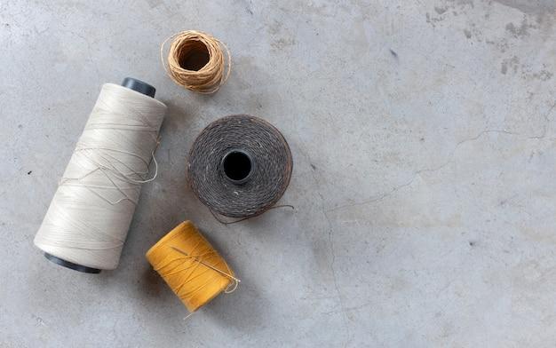 Concetto artigianale e fai-da-te. fili per cucire sul pavimento di cemento. vista dall'alto Foto Premium