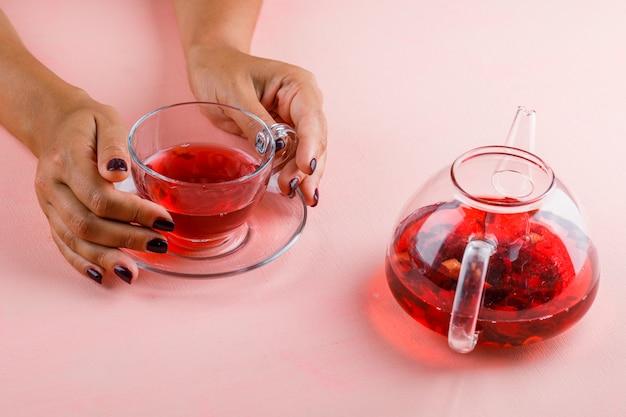 Concetto caldo della bevanda con la teiera sulla donna rosa della tavola che tiene la tazza di vetro di tè. Foto Gratuite