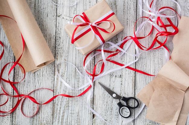 Concetto celebrativo - set con scatola regalo fatta a mano in carta kraft, strumenti da imballaggio, carta da imballaggio Foto Premium