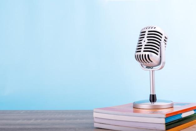 Concetto d'istruzione di istruzione: il retro microfono con molti prenota ha messo sopra la tavola di legno isolata su fondo blu. Foto Premium
