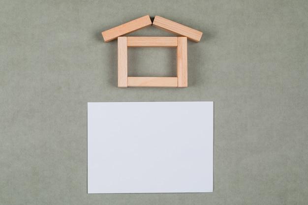Concetto del bene immobile con i blocchi di legno, nota appiccicosa sulla disposizione piana del fondo grigio. Foto Gratuite