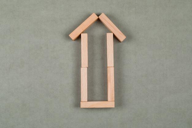 Concetto del bene immobile con i blocchi di legno sulla disposizione piana del fondo grigio. Foto Gratuite