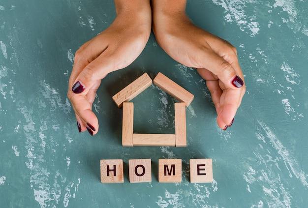 Concetto del bene immobile con la disposizione piana dei blocchi di legno. mani che racchiudono il modello di casa. Foto Gratuite