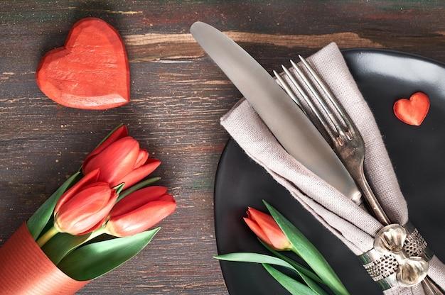 Concetto del menu di primavera con il piatto e la coltelleria giallo-chiaro decorati con i tulipani freschi su legno scuro Foto Premium