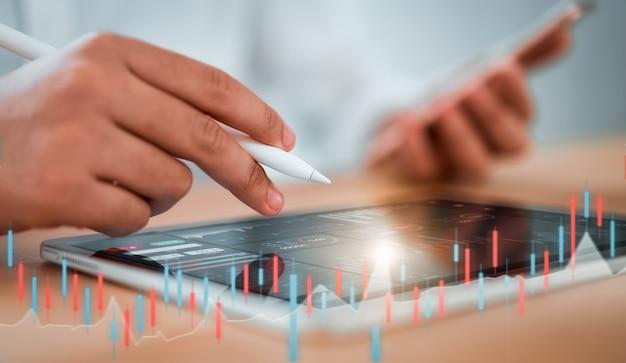 Concetto del mercato di borsa, commerciante dell'uomo d'affari che guarda sulla compressa con la linea della candela di analisi dei grafici nella stanza dell'ufficio, diagrammi sullo schermo. Foto Premium