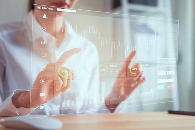 Concetto del mercato di borsa, commerciante della donna di affari che guarda la linea della candela di analisi dei grafici nella stanza dell'ufficio, diagrammi sullo schermo. Foto Premium