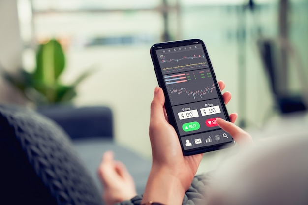 Concetto del mercato di borsa, commerciante della donna di affari che guarda lo smartphone con la linea della candela di analisi dei grafici sul sofà in casa, diagrammi sullo schermo. Foto Premium