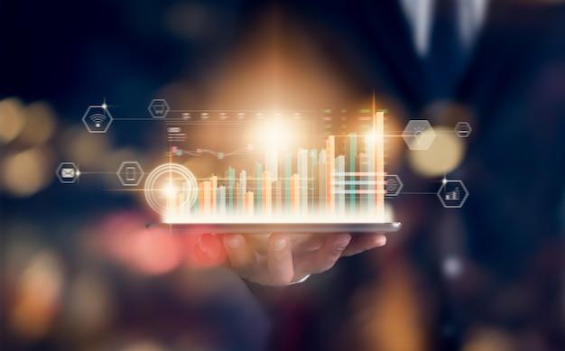 Concetto del mercato di borsa, compressa della tenuta del commerciante della mano con la linea della candela di analisi dei grafici sulla luce di colori del bokeh nella notte. Foto Premium