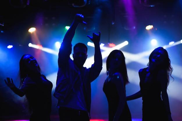 Concetto del partito, di feste, di celebrazione, di vita notturna e della gente - gruppo di amici felici che ballano nel night-club Foto Premium
