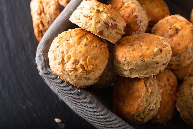 Concetto dell'alimento focaccine al burro butirrose, al prosciutto e al formaggio fatte in casa fresche al forno sul nero Foto Premium