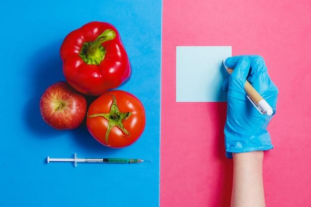 Concetto dell'alimento geneticamente modificato su fondo rosa e blu Foto Premium