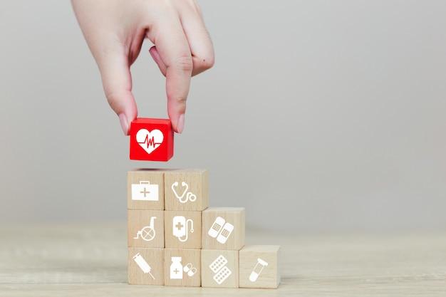 Concetto dell'assicurazione malattia, mano che organizza impilamento del blocco di legno con l'assistenza sanitaria dell'icona medica Foto Premium