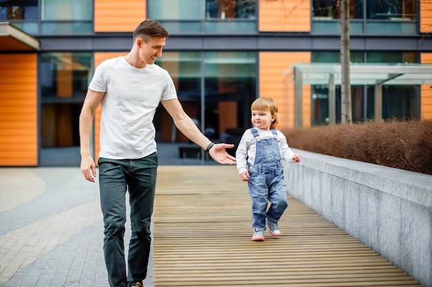 Concetto della famiglia, dell'infanzia, della paternità, di svago e della gente - il giovane padre felice e la piccola figlia passeggiano per le vie della città Foto Premium