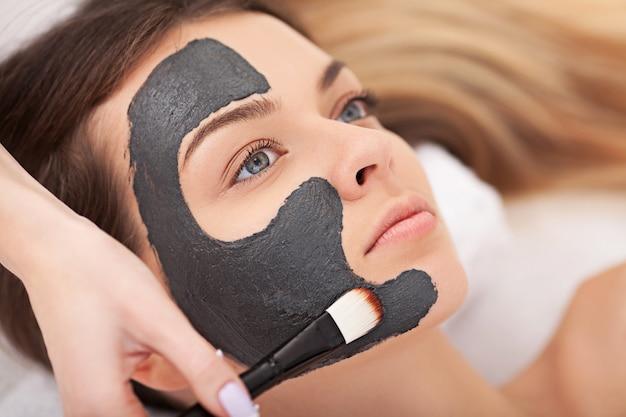 Concetto della gente, di bellezza, della stazione termale, di cosmetologia e di cura della pelle - vicino su di bella giovane donna che si trova con gli occhi chiusi e cosmetologo che applica la maschera facciale dalla spazzola in stazione termale Foto Premium