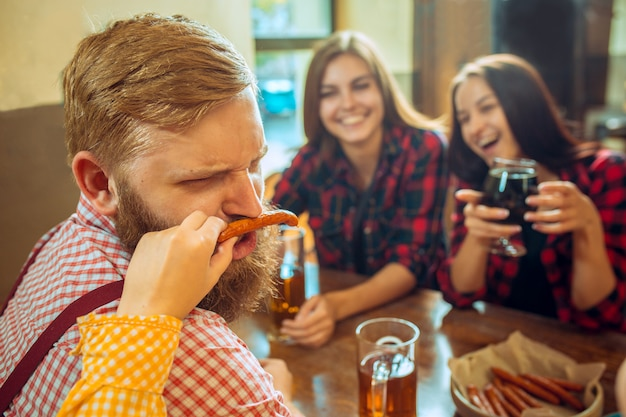 Concetto della gente, di svago, di amicizia e di comunicazione - amici felici che bevono birra, chiacchiere e tintinnio al bar o al pub Foto Gratuite