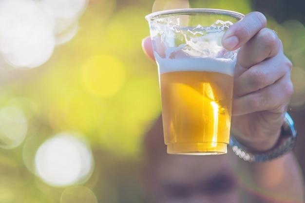Concetto di acclamazioni della birra di celebrazione - mano alta vicina che sostiene i vetri di birra dell'uomo Foto Gratuite