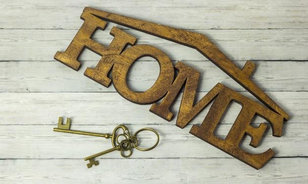 Concetto di acquisizione di abitazioni, la chiave e la casa di parola su un fondo di legno Foto Premium