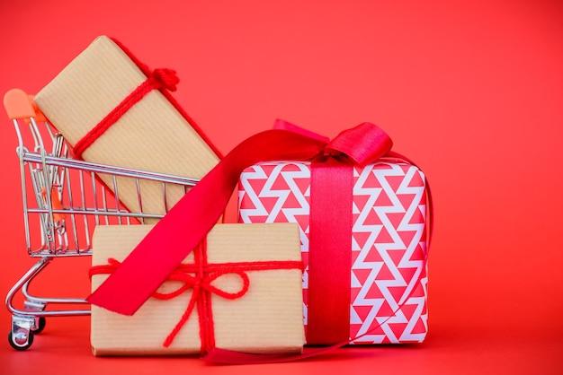 Concetto di acquisto online. carrello e contenitore di regalo su fondo rosso Foto Premium