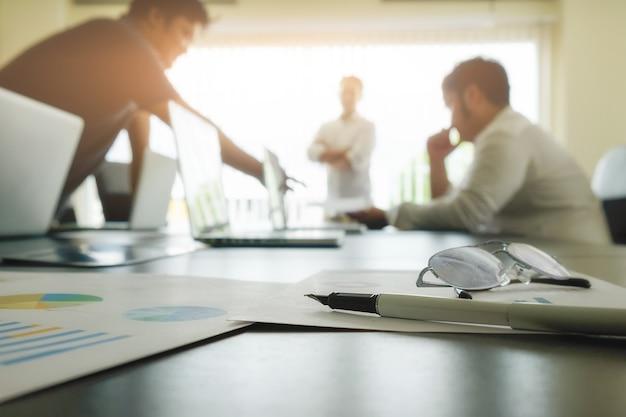 Concetto di affari con spazio di copia. Tavolo da ufficio con penna e diagramma di analisi, computer, taccuino, tazza di caffè sullo scrittorio. Tono di vernice Retro filtro, messa a fuoco selettiva. Foto Gratuite