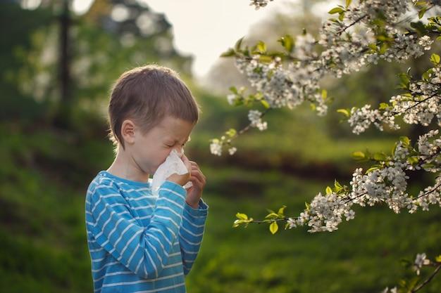 Concetto di allergia il ragazzino sta soffiando il naso vicino ai fiori in fiore Foto Premium