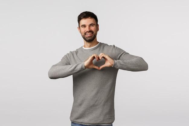 Concetto di amore, famiglia e cura. l'affascinante ragazzo barbuto esprime affetto e teneri sentimenti, fa firmare il cuore sul petto e sorride, ama la relazione, adora il partner, Foto Premium