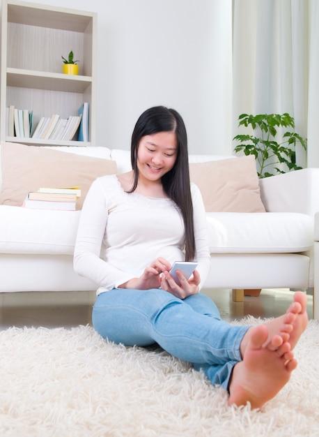 Concetto di app mobili smartphone. ragazza cinese utilizzando uno smart phone. ragazza asiatica rilassata e sdraiata sul soggiorno. Foto Premium