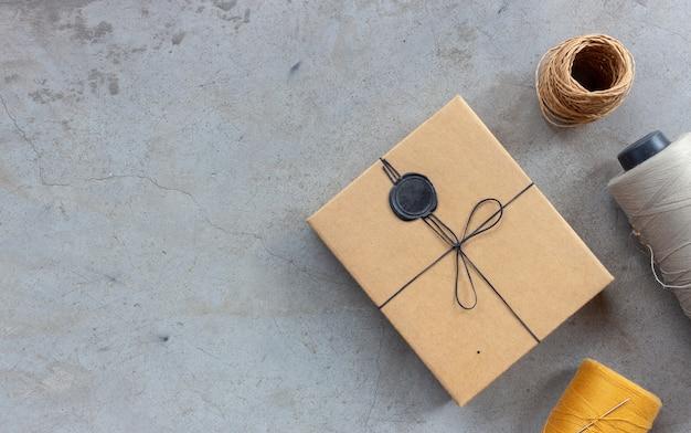 Concetto di artigianato e fai-da-te. fili per cucire e scatole per regali sul pavimento di cemento. vista dall'alto Foto Premium
