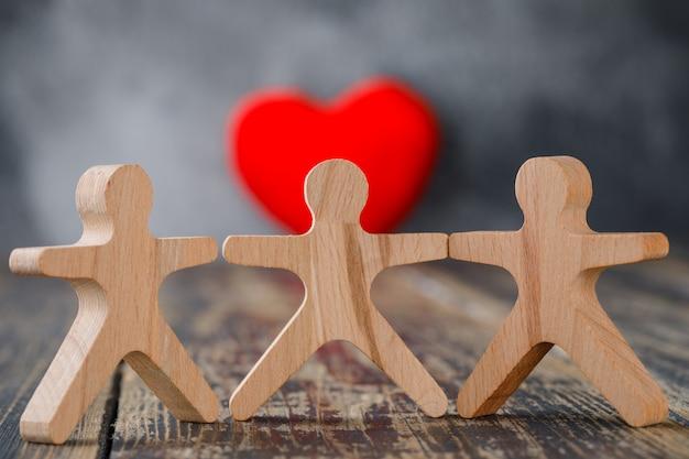 Concetto di assicurazione e di affari con le figure di legno della gente, primo piano rosso del cuore. Foto Gratuite