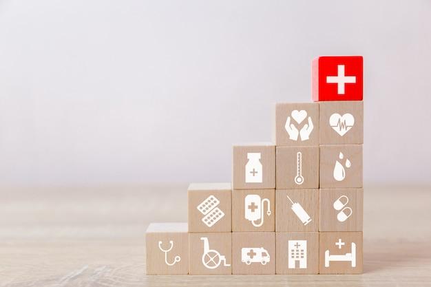 Concetto di assicurazione sanitaria, mano che organizza il blocco di legno che impila con l'assistenza sanitaria dell'icona medica, per salute Foto Premium