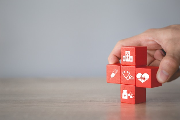 Concetto di assicurazione sanitaria, organizzando l'impilamento del blocco di legno con l'assistenza sanitaria dell'icona medica. Foto Premium