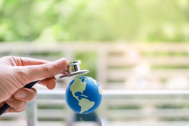 Concetto di assistenza sanitaria globale. primo piano della mano dell'uomo che tiene lo stetoscopio e posato sulla mini palla del mondo. Foto Premium