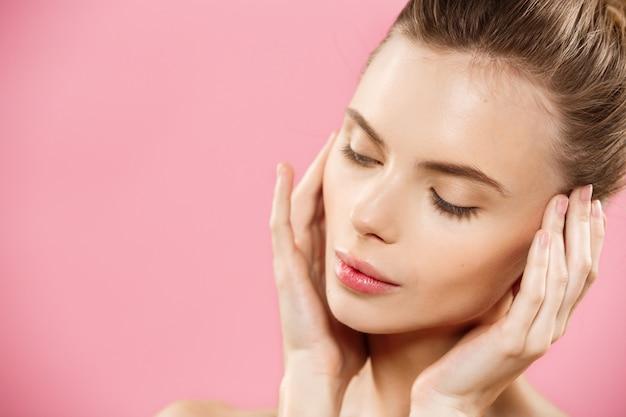 Concetto di bellezza - bella donna caucasica con la pelle pulita, make-up naturale isolato su sfondo rosa brillante con spazio di copia. Foto Gratuite