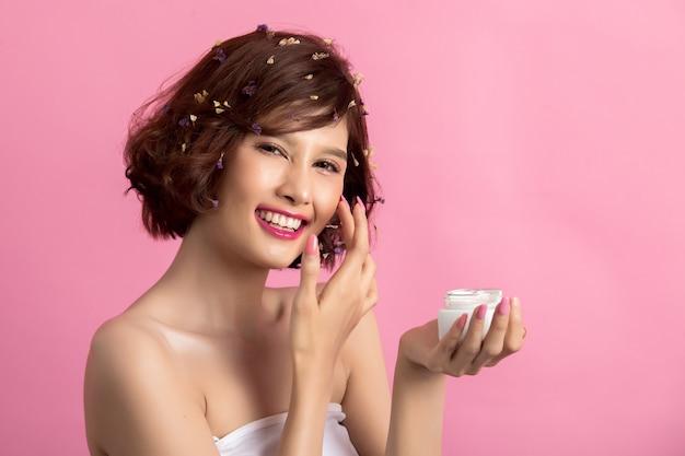 Concetto di bellezza la donna tiene una crema idratante in mano Foto Gratuite