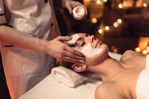 Concetto di benessere con donna con crema in faccia Foto Gratuite