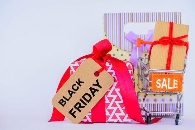 Concetto di black friday. carrello e contenitore di regalo su fondo bianco. Foto Premium