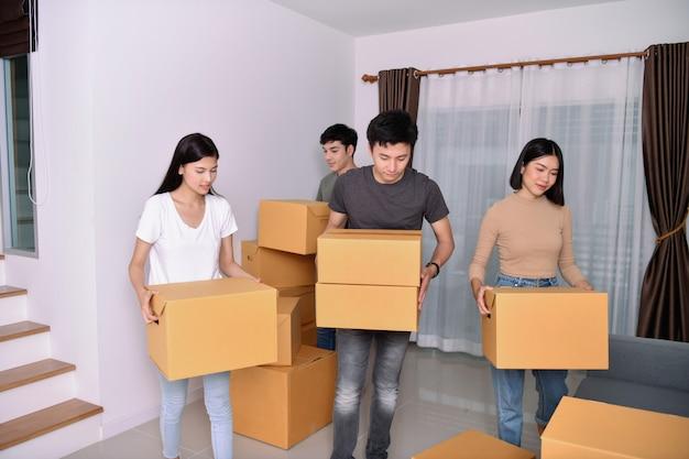 Concetto di casa mobile. i giovani stanno tenendo le loro cose in una scatola di carta. giovane felice nella nuova casa. Foto Premium