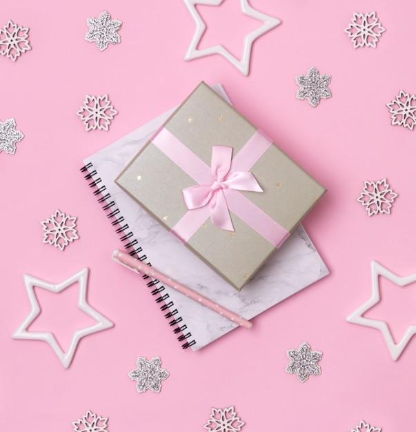 Concetto di celebrazione di inverno natale. blocco note di marmo con la penna e regalo su fondo rosa Foto Premium