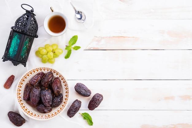 Concetto di cibo e bevande del ramadan. ramadan lantern con tè, datteri frutta, piatto lay. Foto Premium