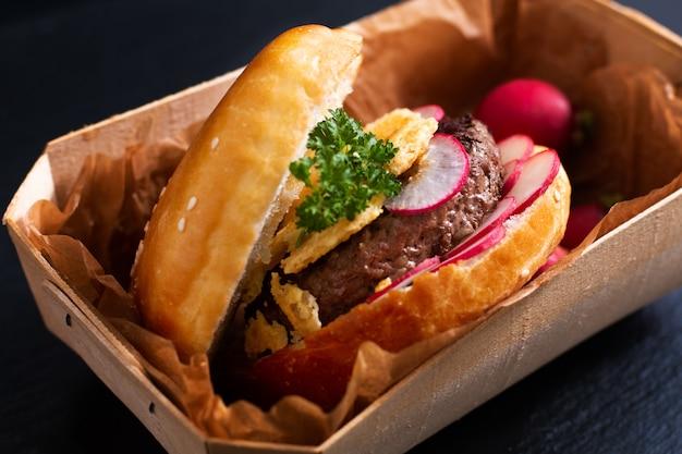 Concetto di cibo homemade organic beefs hamburger con formaggio croccante e ravanello su ardesia nera Foto Premium