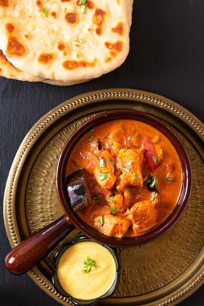 Concetto di cibo in casa tandoori pollo masala al curry con pane naan e salsa di yogurt immersione Foto Premium