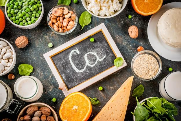 Concetto di cibo sano. set di alimenti ricchi di calcio - latticini e prodotti vegani ca sfondo blu scuro Foto Premium