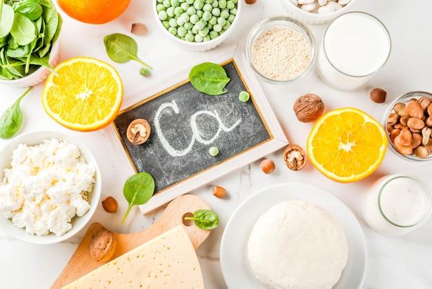 Concetto di cibo sano. set di alimenti ricchi di calcio - prodotti lattiero-caseari e vegani ca sfondo di marmo bianco Foto Premium