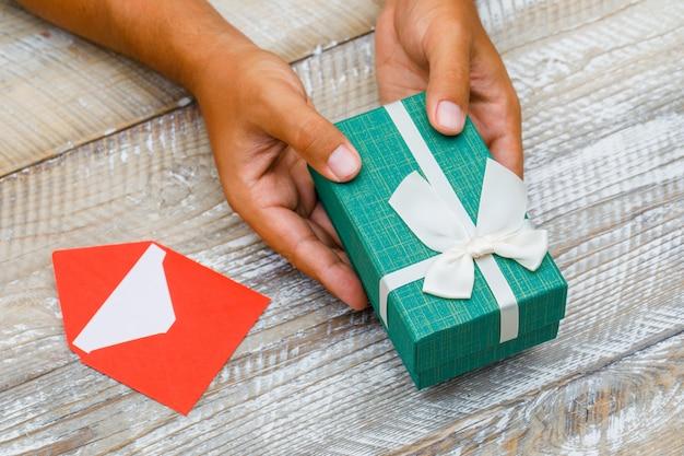 Concetto di compleanno con la carta in busta sulla vista di alto angolo del fondo di legno. uomo che passa confezione regalo. Foto Gratuite
