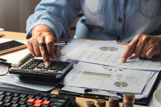 Concetto di contabilità. donna di affari che lavora facendo uso del calcolatore con la pila dei soldi in ufficio Foto Premium