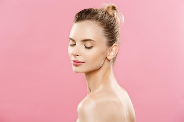 Concetto di cura della pelle - charming giovane donna caucasica con composizione perfetta foto composizione di ragazza bruna. isolato su sfondo rosa con lo spazio di copia. Foto Gratuite